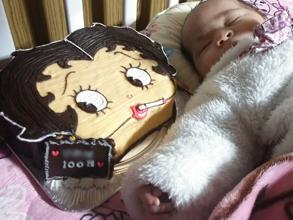 キャラクターの顔型立体ケーキと赤ちゃん